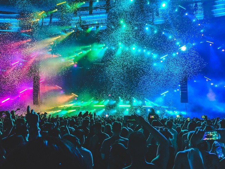 An EDM audience viewing a colorful stage set and a DJ